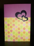 Handmade Valentine's Day card, 70s style, purple banner, multicoloured dots, two hearts embossed in black.