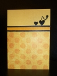 Handmade Valentine's Day card, yellow with orange dots, yellow and black ribbon, small hearts and love bird embossed in black.