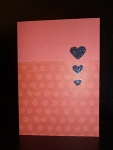 Handmade Valentine's Day card, blood red with three small black glitter hearts.