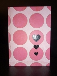Handmade Valentine's Day card with large pink circles embossed with three small black hearts